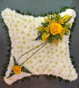 Pillow containing roses, wax flowers and eustoma.