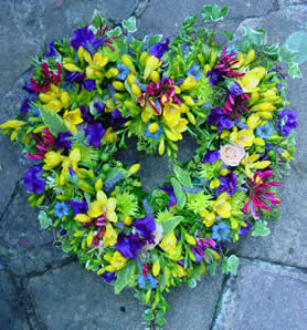 Large colourful open heart of seasonal flowers in yellow, purple with splashes of deep pink.