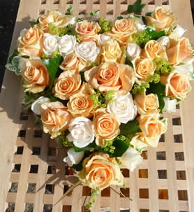 38cm solid heart of roses in gentle creams and pale apricots with foliage.