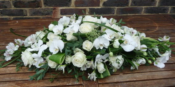Classic white coffin spray teamed with dark green foliage.