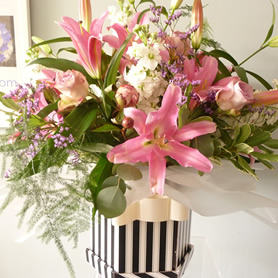 Large hat box of lilies and roses with filler flowers.