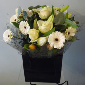 Gift wrapped aqua- packed bouquet of best available seasonal flowers.