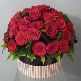Stylish hatbox of large headed red roses and foliage.