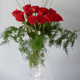 40cm Tall clear glass vase of 12 beautiful luxury red roses with foliage.