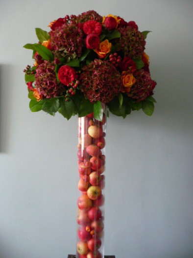 Tall autumnal vase filled with apples and decked with red hydrangeas, red roses and two toned 'Cherry Brandy' roses.