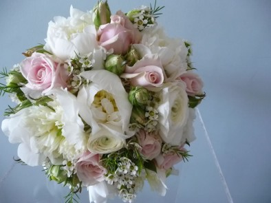 Beautiful wedding bouquet of lightly scented cream peonies, pale pink 'Sweet Avalanche' roses, white wax flowers and herbs.