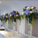 Tall vases of blue hydrangeas, purple eustoma, green spray roses and large headed cream roses