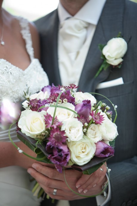 Wedding bouquet of plum coloured tulips and astrantia with ivory roses and tiny wax flowers