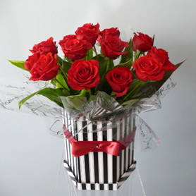 Hat box of beautiful large headed luxury roses with foliage.