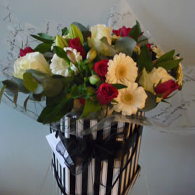 Our stylish vintage hat box filled with 'best available' seasonal flowers.