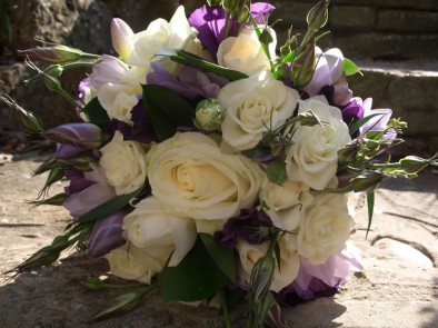 Bridal bouquet of purple eustoma, cream roses and lilac scented freesia.