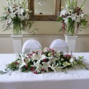 Wedding ceremony set-up with a 'long & low' arrangement and two large vases of scented flowers.