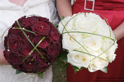 Two compact rose bouquets with grass caging
