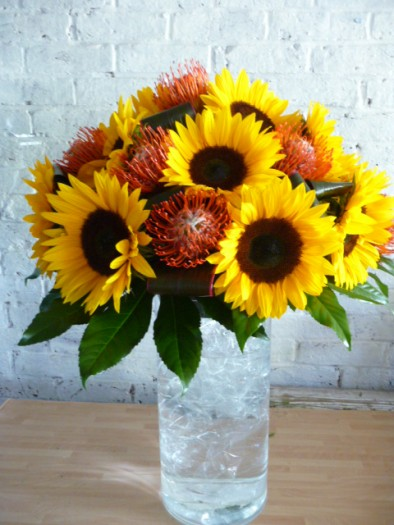 Vase of large headed sunflowers with leucospermum and seasonal foliage.
